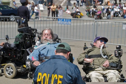Two men in wheelchairs at a political protest.