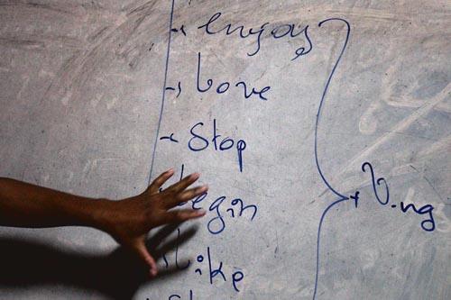 Pheakhdey memberikan pelajaran bahasa Inggris untuk anak-anak penghuni asrama saat malam hari di Vihara di Siem Reap, Kamboja.