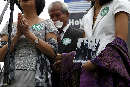 Socheata, Houng and Nin Poeuv pray before adding a family photo to the memorial