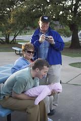 Granny Annie and Grandpa Dana watch daddy Mark try to make Elena smile.
