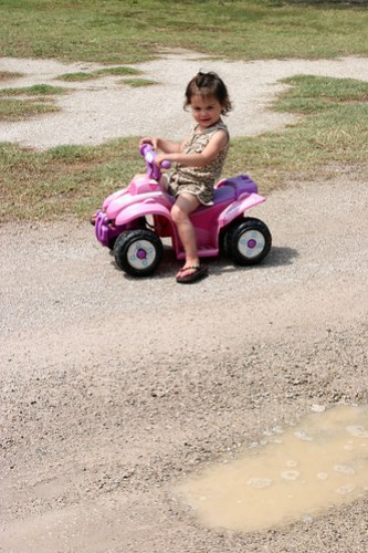 Kaidence rides around the puddles in the campground