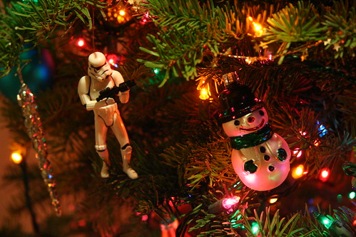 Closeup of a brightly decorated Christmas tree showing a Star Wars Stormtrooper action figure taking aim at a Frosty The Snowman hanging ornament