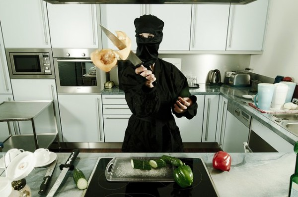 Female ninja cutting food in a kitchen