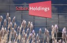 Large dark-glass framed office building with red SabreHoldings sign, foreground showing reeds in landscaping