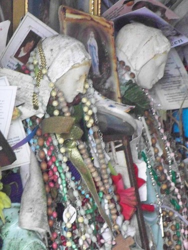 Rosaries draped over statuettes at St. Bridget's Well