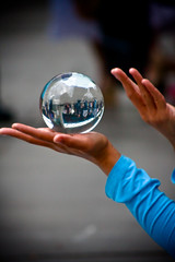 A arm in a bright blue sleeve held up, the hand holding a crystal ball.  Another hand is held open, palm up, a few inches above the ball.