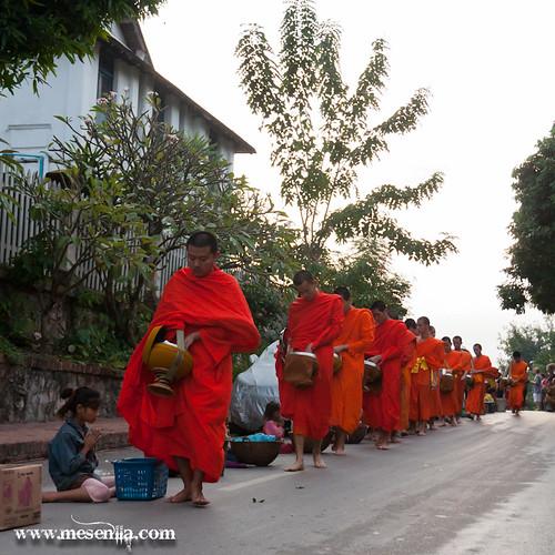 Monjos mendicants donant menjar a nens