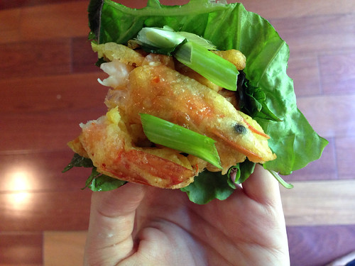 Sweet potato and shrimp fritter on lettuce with onions and herbs.