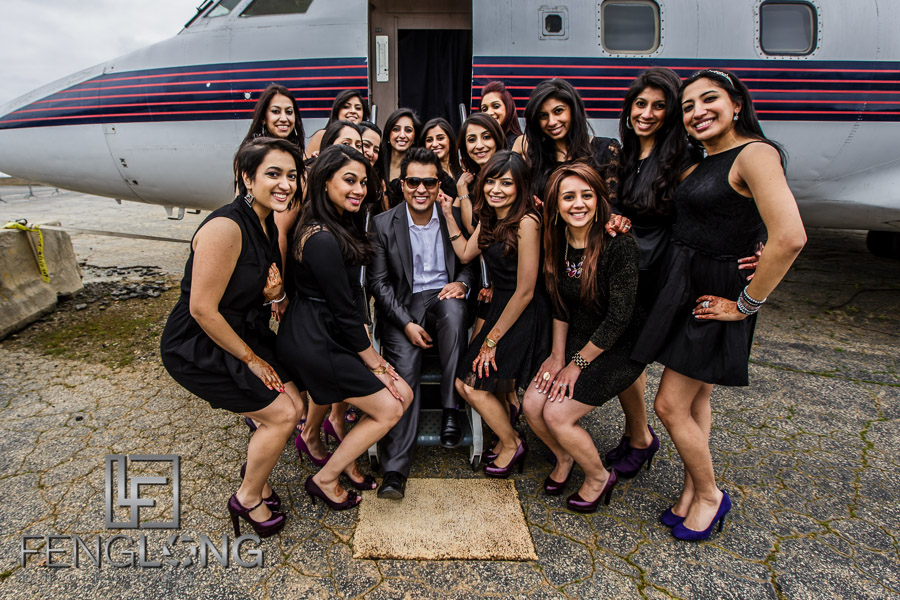 Ismaili Indian groom with bridesmaids in front of airplane for pre-wedding photos
