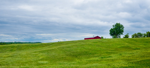 Red barn on a hill.