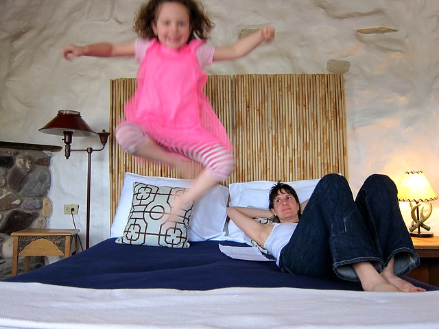 Anais, mid-air, jumping on the bed at La Posada Milagro, with Maile looking on