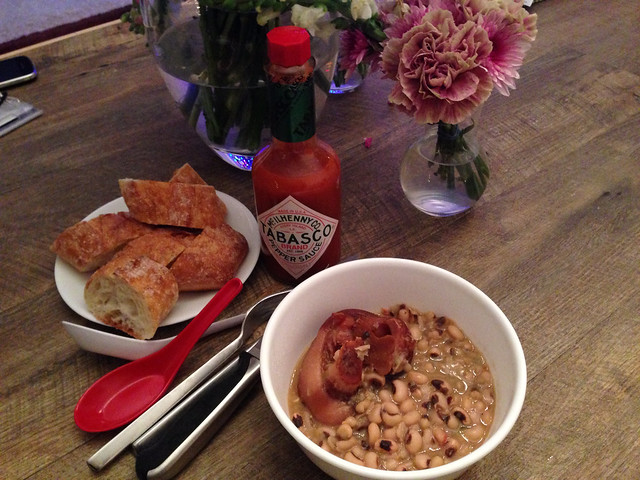 Black eyed pea stew with smoked ham hock, served with sliced bread and Tabasco hot sauce