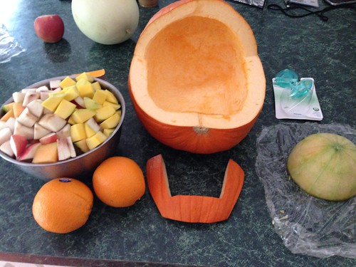 Cut pumpkin for baby carriage, sliced fruit, and cantaloupe baby head