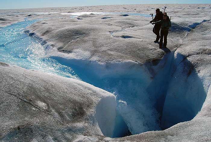A stream of meltwater on the surface of the Greenland Ice Sheet enters a moulin connecting to the glacier's bed, 700 meters below