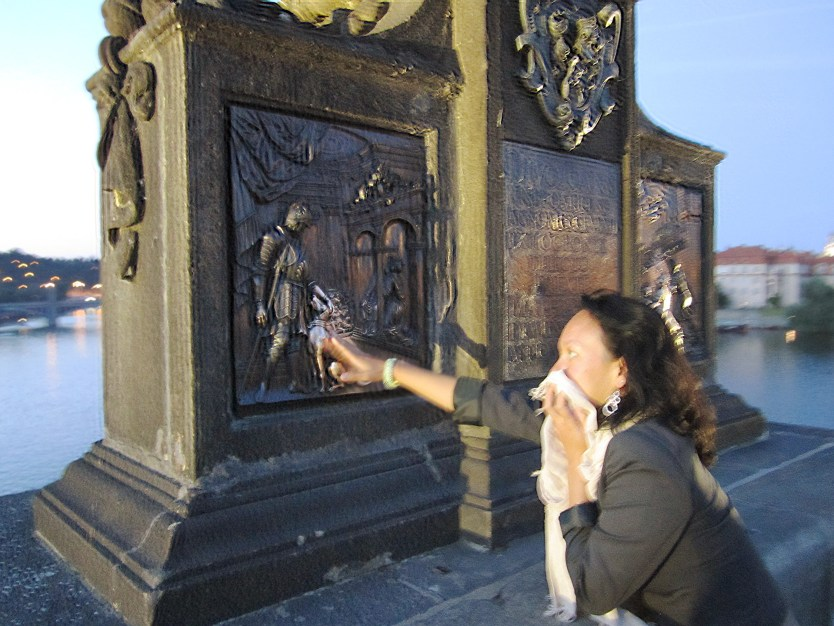 Heather touching the lucky dog on the Charles Bridge while dodging the bugs.