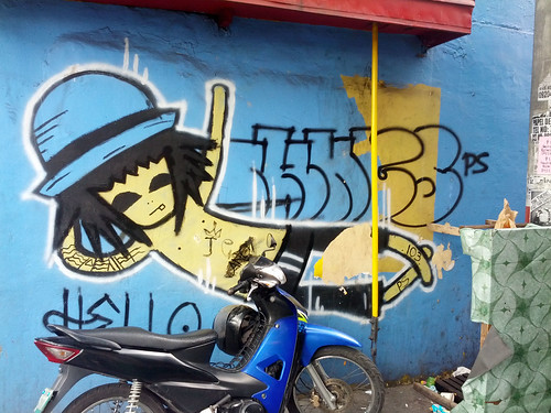 graffiti on a blue wall behind a motorcycle