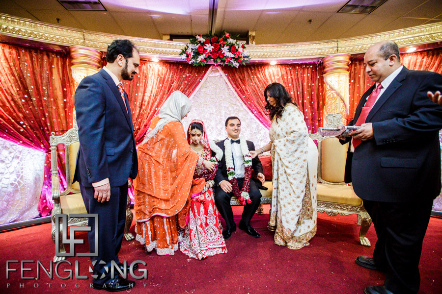 Bride and groom receive wedding garlands from parents