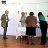 24. Following his talk, Mr. Hillier walks toward the beverage table attended by member Danuta Buzdygan.