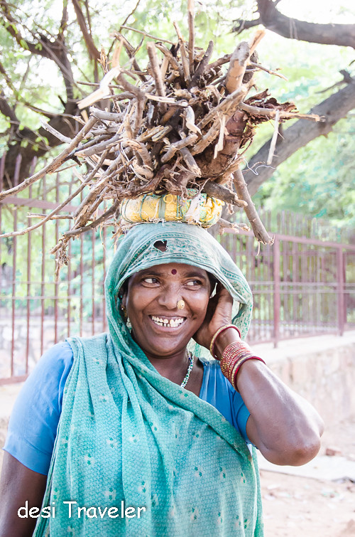 smiling women with pile of wood on head