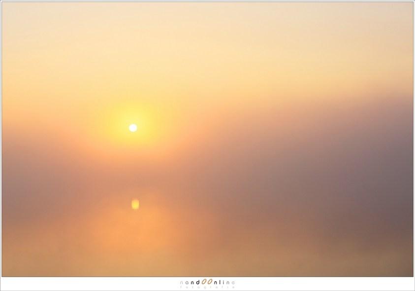 De zon hangt geheimzinnig boven het water