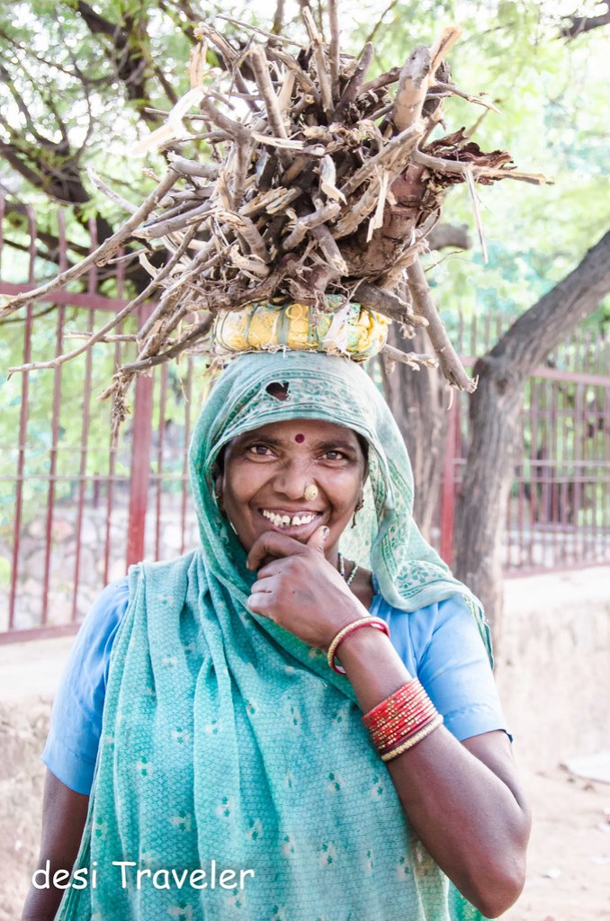 smiling woman wearing bangles with fire wood on her head