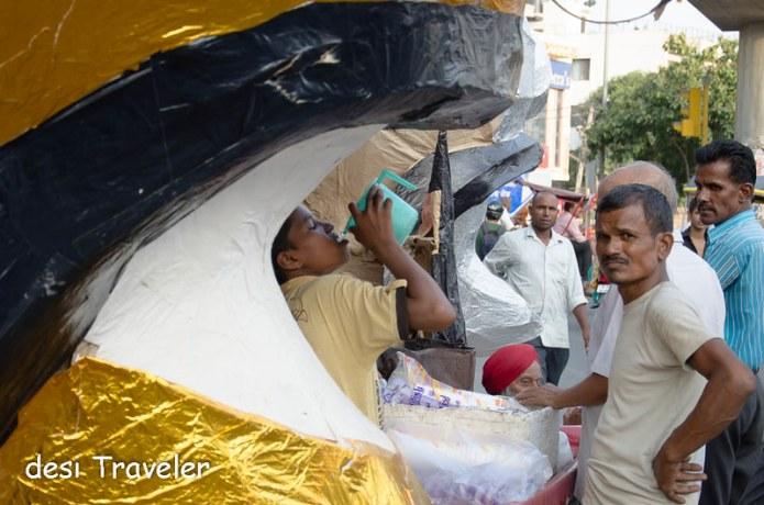 Boy drinking water from plastic mug next to a Ravana