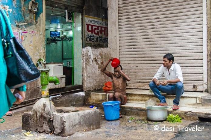 A boy taking bath from handpump India