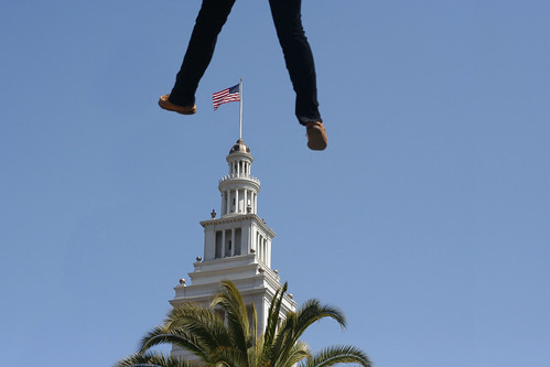 legs dangling from the sky, framing the clocktower at SF Ferry Building