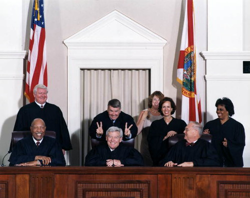"""Harry Anstead putting """"rabbit ears"""" on Charles Wells prior to formal en banc portrait of Florida Supreme Court Justices from the year 2000"""