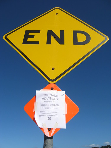 A photograph of a pole holding two signs. The top sign is a yellow diamond which reads 'END,' indicating the end of a road. The bottom sign is a reflective orange diamond mostly obscured with a paper notice reading 'tsunami advisory' which has been taped on. The notice goes on to say: 'February 27 2010 avoid beaches, low lying areas, surfing, swimming, and boating. Dangerous riptides are also expected. Avoid all water contact. Affected areas: Eastern Pacific Coast, including Mendocino County. Expected maximum wave height: Approx two feet. Precipitating event: An 8.8 magnitude earthquake in Chile.' The bottom of the notice bears the seal of the City of Fort Bragg, with a redwood tree and a splashing salmon.