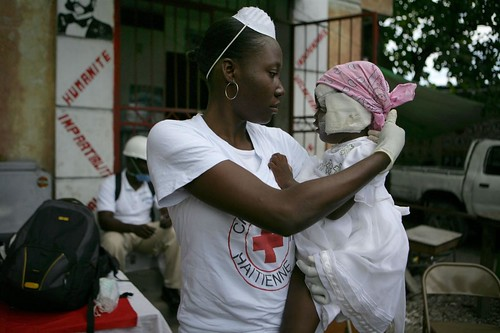 Haitian Red Cross volunteer Miname Glaude holds Michel Laurent (15 months) at a Red Cross medical center in Croix de Priez