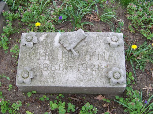 "Rectangular grave stone with an open flower in each corner and a hand in the top center clutching a tool, possibly a brush.  The stone reads ""John Hoffman, 1868-1926"""