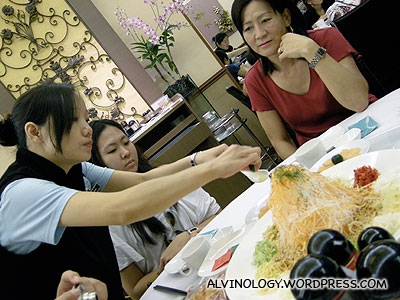 The waitress adding in all the ingredients for the Yu Sheng