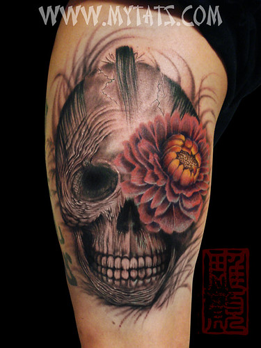 Black and gray skull with color on the Peony flower. Tattoo on the thigh and