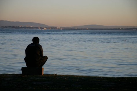 Man looking out over the River Tagus, Lisbon, Portugal