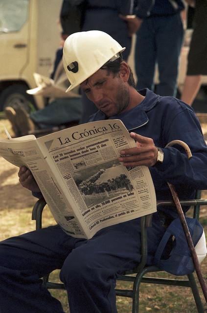 Minero leyendo las noticias de la Marcha Negra en la prensa.