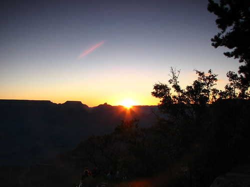 the sun rises over the rim of the grand canyon