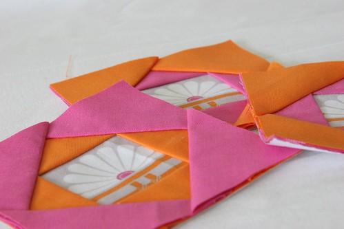 Three pink and orange paper pieced blocks
