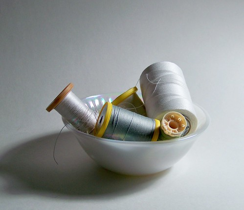 white glass bowl with spools of neutral color cotton thred