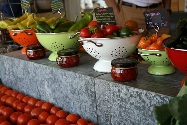 Four colanders in orange, lime green, and white are filled with vegetables on a granite counter top