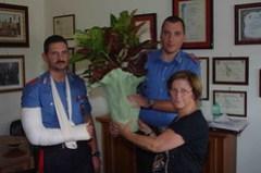 Consegna pianta ai CC soccorritori da parte madre di un ragazzo coinvolto