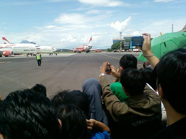 Beberapa pengunjung yang membawa kamera atau pun ponsel berkamera, mengabadikan pesawat Air Asia yang hendak lepas landas. (Foto: Yudha PS)