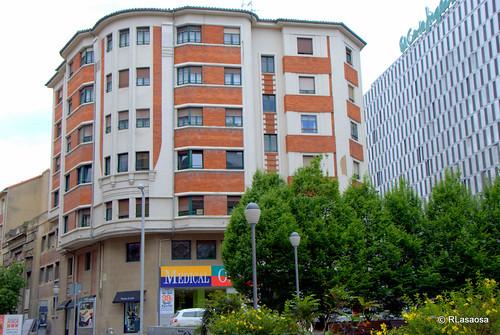Edificio de viviendas en la calle Estella, con fachadas a la plaza del Vínculo y calle Sancho el Mayor. A la derecha, fachada a la calle Tudela de El Corte Inglés.