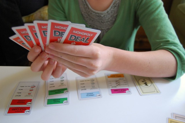 """A person holding a hand of """"Monopoly Deal"""" cards."""