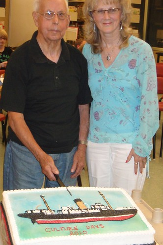 Gus Menchions [95 years old] cuts Kyle cake with Sandra Roach of the Bay Roberts Cultural Foundation