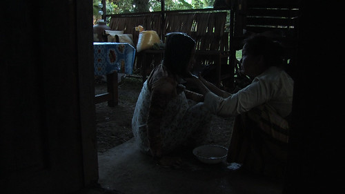 Farida applies coconut milk on Ayesah's hair