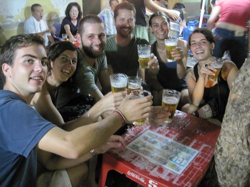 flanqueados por un suizo y una francesa, cuatro catalanes fotografiados por una quinta, brindando con la Bia Hoi, la cerveza fría de barril popular en Hanoi, Vietnam