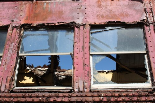 The inside of an abandoned train car, showing that the roof is missing several panels and allowing the sky to show through.