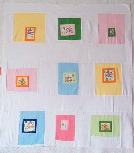 modern patchwork quilt top - square in square with fussy cut centers - pink, orange, yellow, green and blue.