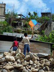 Kinder lassen Drachen steigen auf Schutthaufen